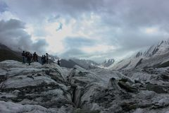 A snow covered mountain Rakaposhi altitude of 13000 ft and Minapin Glacier with clouds in the sky Stock Images
