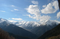 Snow covered mountain range. Panoramic view of a snow covered mountain range in the Black Sea region of Turkey with blue sky and clouds in the background Royalty Free Stock Image