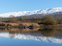 Snow covered mountain range reflected in lake at Butcher's Dam, Central Otago, New Zealand Royalty Free Stock Photography