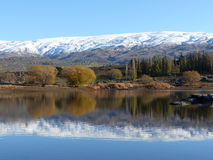 Snow covered mountain range reflected in lake at Butcher's Dam, Central Otago, New Zealand Royalty Free Stock Images
