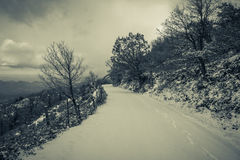 Snow covered mountain road with footsteps and sea view beyond Royalty Free Stock Image
