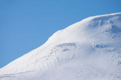 Beautiful snowy mountains with blue sky in the background. Snow-covered mountain on a sunny winter day with some avalanche danger Stock Photography