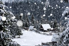 Snow covered mountain wooden cabin. Snow covered mountain wooden hut during snowstorm blizzard. Chalet in the mountains at winter Royalty Free Stock Image
