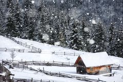 Snow covered mountain wooden chalet. Snow covered mountain wooden hut during heavy snowing. Cabin in the mountains at winter Stock Image