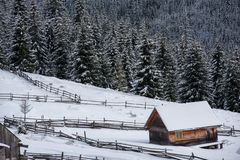 Snow covered mountain wooden chalet. Snow covered mountain wooden hut. Cabin in the mountains at winter Royalty Free Stock Images