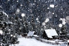 Snow covered mountain wooden hut. During heavy snowing. Cottage in the mountains at winter Stock Images