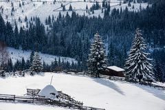 Snow covered mountain wooden hut. Cottage in the mountains at winter Royalty Free Stock Image