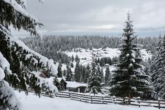 Snow covered mountain wooden hut. Cottage in the mountains at winter Royalty Free Stock Photo