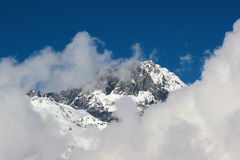 Snow covered mountains against white clouds and blue sky, Georgi. A, Caucasus mountains Stock Photography