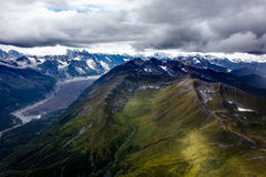 Snow covered mountains in background of green mountains and glacial valley Royalty Free Stock Photography
