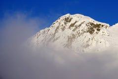 Beautiful alpine landscape with fog in winter. Fagaras Mountains. Snow covered mountains at Balea Lake Resort, Transylvanian Alps, Romania, Europe Stock Image