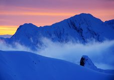 Beautiful alpine landscape at sunset with clouds and sea clouds. Fagaras Mountains in winter. royalty free stock photos