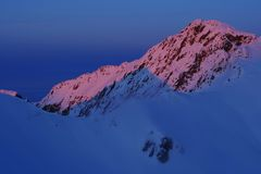 Beautiful colored alpine landscape with sunset in winter. Fagaras Mountains. Snow covered mountains at Balea Lake, Transylvanian Alps, Romania, Europe Royalty Free Stock Images