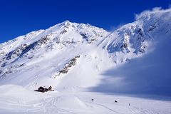 Beautiful landscape with wooden chalet, blue sky and sunshine in winter. Fagaras Mountains Stock Images