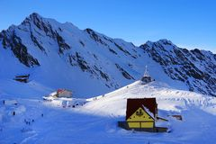 Beautiful landscape with wooden chalet, blue sky and sunshine in winter. Fagaras Mountains Stock Photography