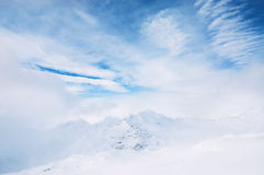 Snow-covered mountains and blue sky. With white clouds. Beautiful winter landscape Stock Photos