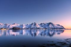 Snow covered mountains and colorful sky reflected in water. Beautiful snow covered mountains and colorful sky reflected in water at night. Winter landscape with royalty free stock photo