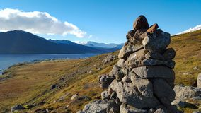 Snow covered mountains in the distance in autumn. With stacked rocks in Iceland Stock Photography