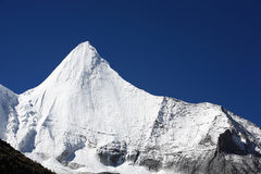 Snow covered mountains. A snow covered mountain peak under clear blue skies Stock Photography