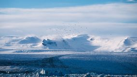 Snow Covered Mountains Next to the Ocean Water Under the Clouds Royalty Free Stock Images