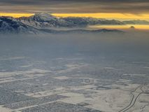 Snow covered mountains overlooking Salt Lake City in winter with glow of rising sun royalty free stock image