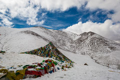 Snow covered mountains. And prayer flags in Tibet Stock Photography