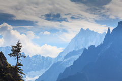 Snow covered mountains and rocky peaks in the French Alps. Snow covered mountains, clouds and rocky peaks in the French Alps Royalty Free Stock Image