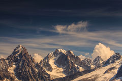 Snow covered mountains and rocky peaks in the French Alps. Snow covered mountains, clouds and rocky peaks in the French Alps Stock Image