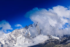 Snow covered mountains and rocky peaks in the French Alps Stock Images