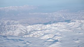 Snow covered mountains in sunny weather, high altitude aerial view stock video