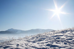 Snow covered mountains under blue sky. Horizontal snow covered mountains under blue sky and shiny sun Stock Photos
