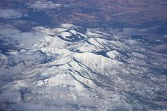 Snow-covered mountains viewed from airplane. Somewhere above USA royalty free stock photo