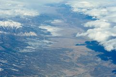 Snow-covered mountains viewed from airplane. Somewhere above USA Stock Photos