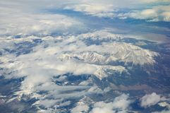 Snow-covered mountains viewed from airplane. Somewhere above USA royalty free stock photography