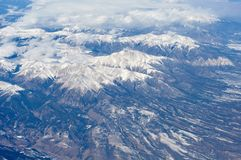 Snow-covered mountains viewed from airplane. Somewhere above USA stock image