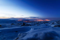Snow-covered mountainside, night photo. In the distance the steel mills. Royalty Free Stock Photos