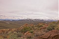 Snow Covered Nevada Mountains. Nevada Mountains on the horizon with rolling brush land in the valley. Rocks in the foreground give overall depth to photo Royalty Free Stock Photo