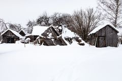 Snow-covered old abandoned courtyard in village. Snow-covered old abandoned courtyard in typical russian village in winter day in Smolensk region of Russia Royalty Free Stock Photos