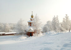 Snow covered orthodox chapel amidst winter grove on the background of hoary forest Royalty Free Stock Photos