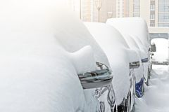 Snow covered ows of cars in the parking lot. Urban scene, snowstorm. Clean automobile from the snow. Snow covered ows of cars in the parking lot. Urban scene Royalty Free Stock Images
