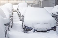 Snow covered ows of cars in the parking lot. Urban scene, snowstorm. Clean automobile from the snow. Snow covered ows of cars in the parking lot. Urban scene Stock Photos