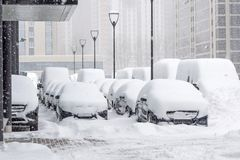 Snow covered ows of cars in the parking lot. Urban scene, snowstorm. Clean automobile from the snow. Snow covered ows of cars in the parking lot. Urban scene Stock Photography