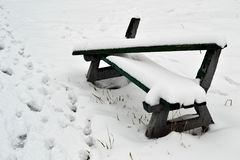 A snow covered park bench. Abandonned bench in a snow filled field with trees in background royalty free stock photos