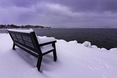 Snow covered park bench on Okanagan Lake West Kelowna British Columbia Canada Royalty Free Stock Photos