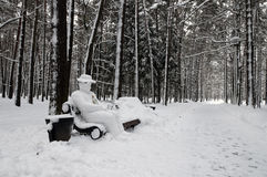 Snow-covered park bench with yeti man Stock Images