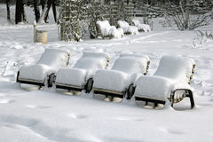 Snow-covered park-chairs in a municipal park Stock Images