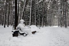 Snow-covered Parkbank mit Yetimann Stockbilder