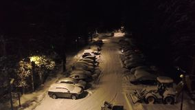 Snow-covered parking in forest. Clip. Top view of parking with snow-covered cars and standing bulldozers to clean snow. On background of forest at night stock footage