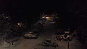 Snow-covered parking in forest. Clip. Top view of parking with snow-covered cars and standing bulldozers to clean snow. On background of forest at night stock video footage