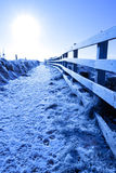 Snow covered path on cliff fenced walk Royalty Free Stock Images